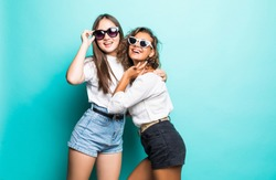 Friends forever. Two cute lovely girl friends in sunglasses posing with smile on blue background