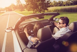Friends, friendship, destination, auto vehicle rent, escape, speed ride. Rear back shot of carefree wife driver with arms rudder and henpecked husband on way to honeymoon, sunshine, sunlight, light