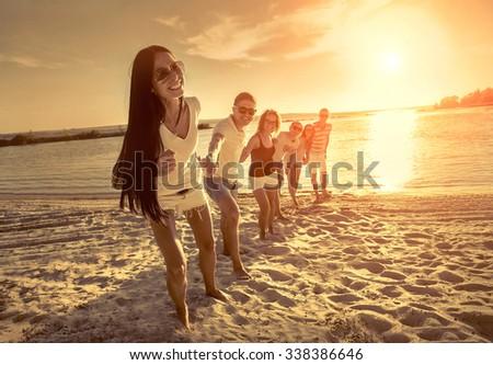 Friends fun on the beach under sunset sunlight. #338386646