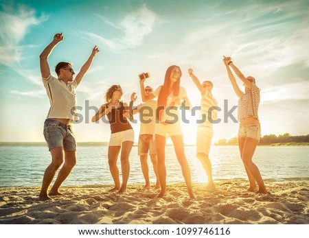 Friends funny dance on the beach under sunset sunlight. Sunny day and friendship. #1099746116