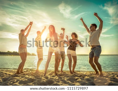 Friends funny dance on the beach under sunset sunlight. Sunny day and friendship. #1115729897