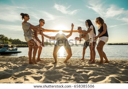 friends funny game on the beach ...