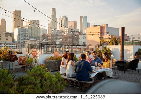 Friends Gathered On Rooftop Terrace For Meal With City Skyline In Background #1151225069