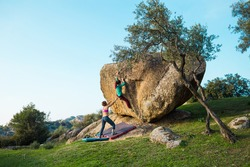 Friends go in for sports in nature, bouldering on rocks, girl climbs a big stone, woman is belayng partner, outdoor recreation, bouldering on the boulders of Lake Bafa
