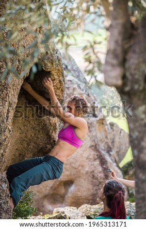 Friends go in for sports in nature, bouldering on rocks, girl climbs a big stone, woman is belayng partner, outdoor recreation, bouldering on the boulders of Lake Bafa Stock photo ©