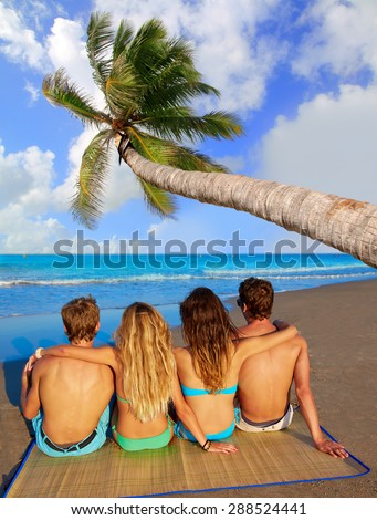 friends group couples sitting in beach sand rear view back palm tree photo mount