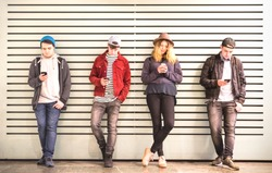 Friends group using smartphone against wall at university college backyard break - Young people addicted by mobile smart phone - Technology concept with always connected millennials - Bright filter