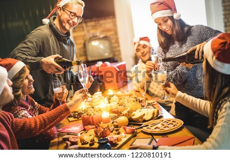 Friends group with santa hats celebrating Christmas with champagne and sweets food at home dinner - Winter holidays concept with people enjoying time and having fun eating together - Warm filter - Shutterstock ID 1220810191