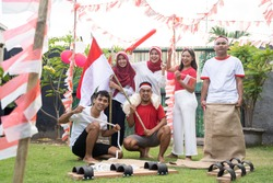 Friends groups gather wearing red and white clothes carrying Indonesian flags with bamboo sticks and race equipment to commemorate the Independence Day celebrations in the yard