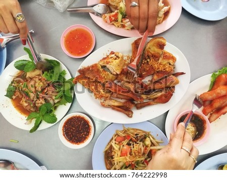 Friends happiness enjoying eating traditional  Northeastern Style of Thailand such as Papaya salad (Som Tam), grilled Chicken, Charcoal-boiled pork neck,Ground pork salad #764222998