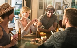 Friends having a drink and playing cards on a sunny evening. They are sitting at a wooden table in a cozy house with beers and tortilla chips. They are smiling, wearing casual clothes and hats.