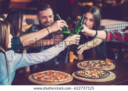 Friends having a drinks in a bar, They are sitting at a wooden table with beers and pizza. stock photo