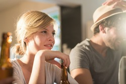 Friends having a drinks on a sunny evening. A blonde girl and a boy with beard and hat are sitting close to each other in a cozy house with beers and tortilla chips. They are wearing casual clothes