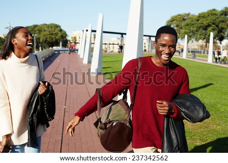 Friends having a great time together, two college friends laughing having good time, african couple smiling each to other at beautiful day two students smiling at college campus, happy people laughing