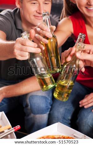 Friends having a nice little party with beer an pizza, they clink their glasses and have lots of fun