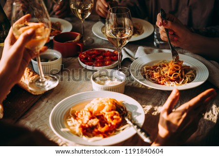 Friends having a pasta dinner at home of at a restaurant. #1191840604