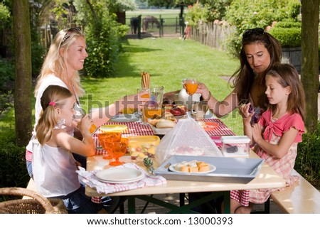 Friends having a picnic outdoors on a summer's day