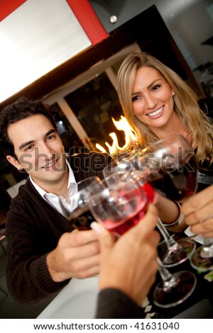 Friends having dinner and toasting at a restaurant
