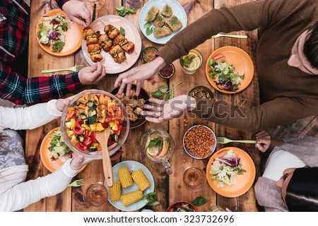 Friends having dinner. Top view of four people having dinner together while sitting at the rustic wooden table #323732696