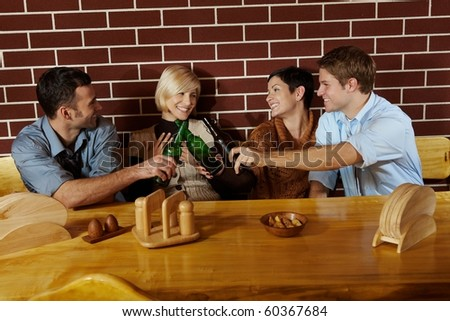 Friends having fun at bar, sitting together at table, having beer, laughing.?