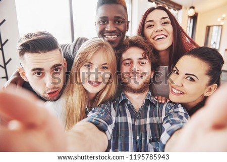 Friends having fun at restaurant. Three boys and three girls making selfie and laughing. On foreground boy holding smart phone. All wear casual clothes.