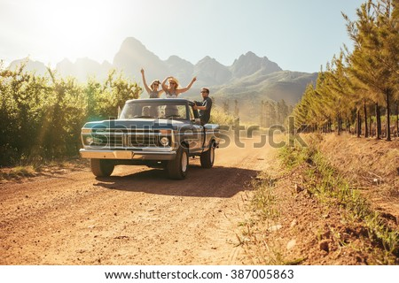Friends having fun in the open back of a vintage truck on a summer day in countryside. Young men and woman enjoying on a road trip.