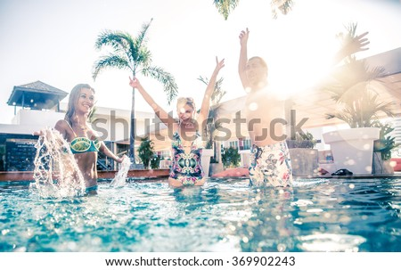Friends having party and dancing in a swimming pool - Young people enjoying vacation in a tropical resort hotel