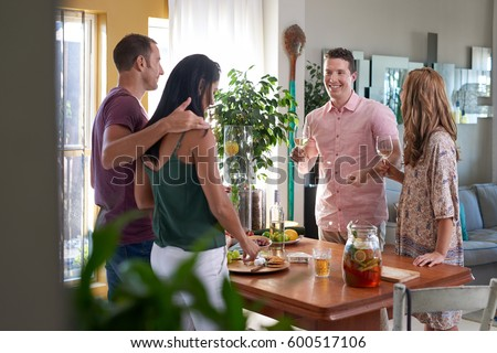 Friends having small party at home, intimate warm social gathering with wine cheese and biscuits