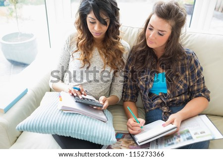 Friends helping each other with homework on sofa using calculator and notepads