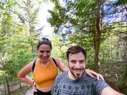 Friends hiking in the woods during summertime, taking a selfie.