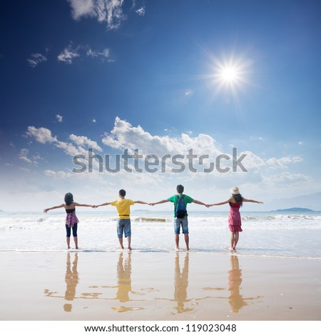 friends holding together on beach - stock photo