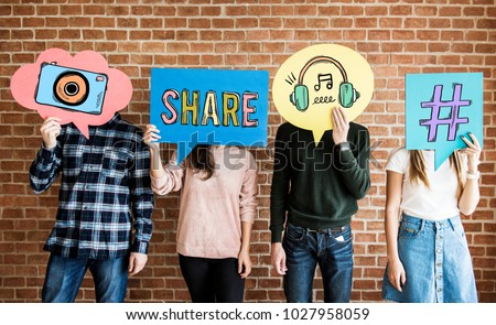 Friends holding up thought bubbles with social media concept icons #1027958059