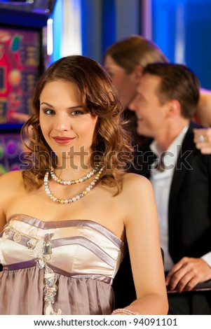 Friends in Casino on a slot machine; a woman is looking into the camera