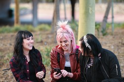 friends in city hanging out college students laughing having fun with punk girl using smartphone in city