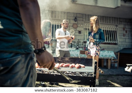 Friends in home garden grilling meat and having fun - Group of people at barbecue party drinking wine