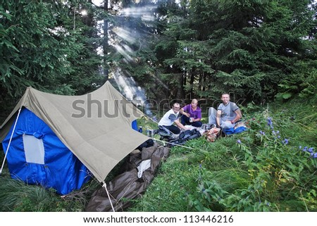 Friends in the campaign with a tent in the Carpathian forest.