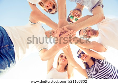 Friends joining hands while standing huddle, down view photo