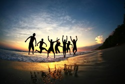 Friends jumping for joy on tropical beach at sunset in a group formation