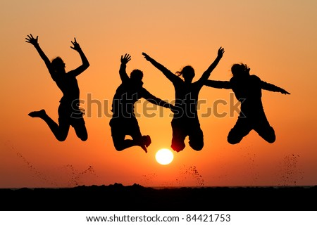 friends jumping in sunset