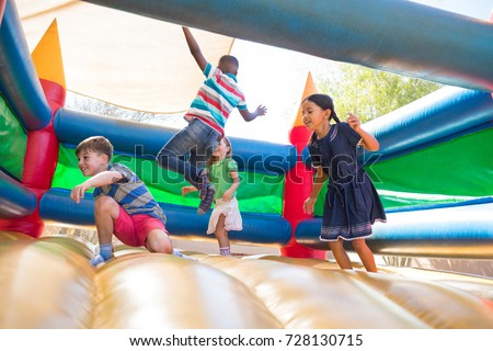 Friends jumping on bouncy castle at playground