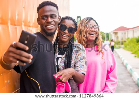 friends laughing while viewing something on a mobile phone. #1127849864