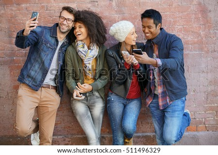 Friends leaning on brick wall, playing with smartphones