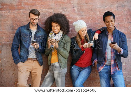 Friends leaning on brick wall, playing with smartphones #511524508