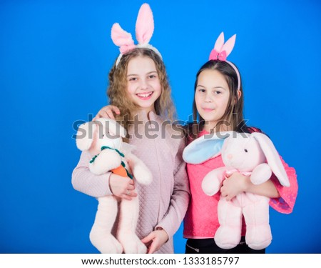 Friends little girls with bunny ears celebrate Easter. Children with bunny toys on blue background. Sisters smiling cute bunny costumes. Spread joy and happiness around. Hope love and joyful living. #1333185797