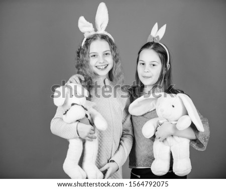 Friends little girls with bunny ears celebrate Easter. Children with bunny toys on blue background. Sisters smiling cute bunny costumes. Spread joy and happiness around. Hope love and joyful living.