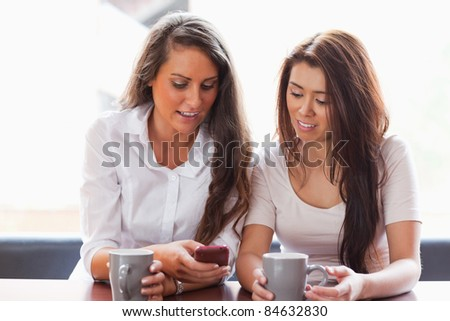 Friends looking at a smartphone while having a coffee
