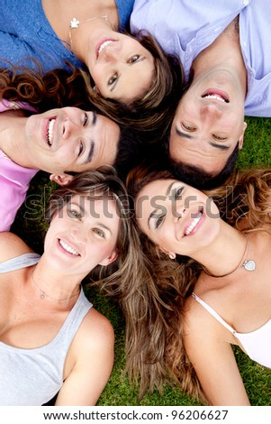 Friends lying down outdoors in a circle and smiling - stock photo