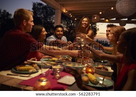 Friends make a toast at a dinner party on a patio, close up ストックフォト ©