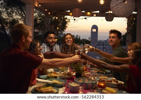 Friends make a toast at a dinner party on a patio, close up