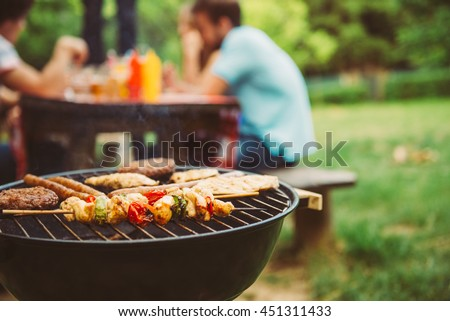 Photo of  Friends making barbecue and having lunch in the nature.